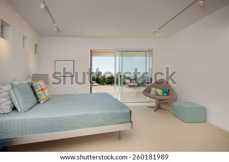 Modern eclectic bedroom with ceiling lights and french sliding doors leading to outdoor view deck. King size bed with designer elements in amazing bedroom. - stock photo
