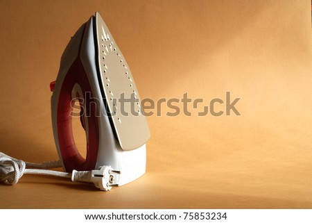 Modern electric iron standing on nice gold background with sun lighting