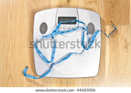 Modern electronic scales with blue tape measure across it on a wooden floor symbolising dieting