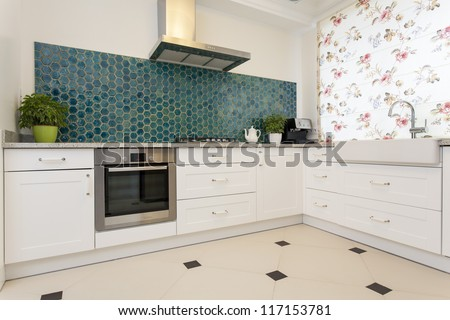 Modern elegant kitchen with turquoise wall - stock photo