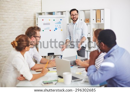 Modern employees listening to handsome teacher explaining subject at seminar - stock photo