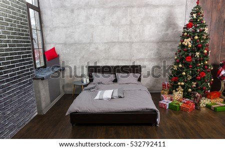 Modern empty bedroom in loft style with grey colors and Christmas tree with presents, bed with grey blanket