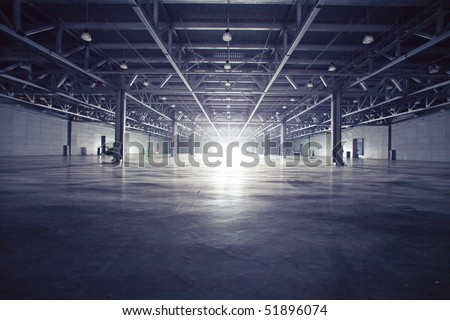 Modern empty dark storehouse with light at the end - stock photo