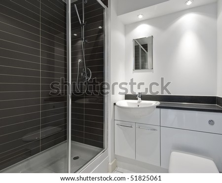 modern en-suite bathroom with a shower cabin and dark ceramic tiles - stock photo