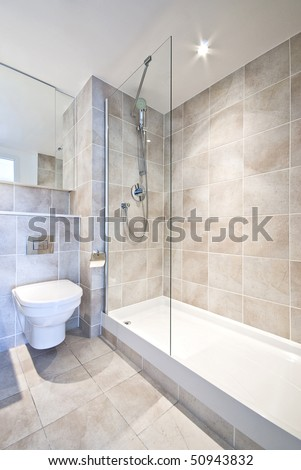 Modern en suite bathroom with large shower, toilet and wash basin in beige natural with natural stone tiled walls - stock photo