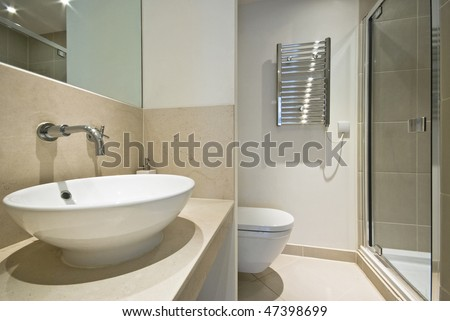 Modern en-suite bathroom with round ceramic hand wash basin, toilet and shower - stock photo