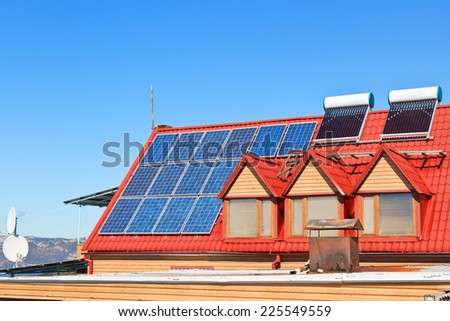 modern energy-saving technology - Solar Batteries and heaters on house roof - stock photo