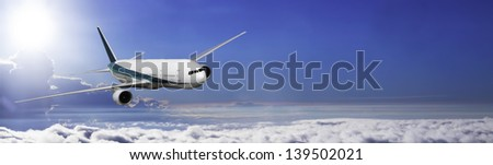 Modern 2 engine airliner banner on sky with horizon visible. - stock photo