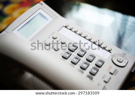 Modern executive VoIP desk phone with traditional corded headset. Shallow depth of field - focus on the center of the image. - stock photo