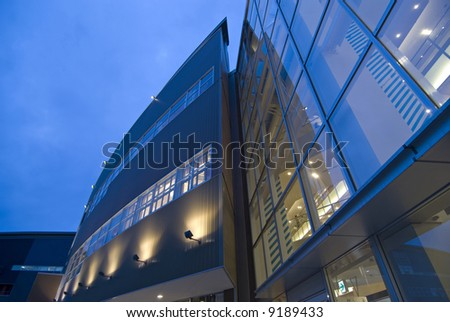 modern exterior  abstract architectural background with wall and window illumination and blue sky - stock photo