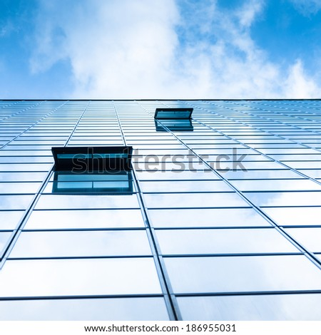 Modern facade of glass and steel with open window reflecting sky and clouds.