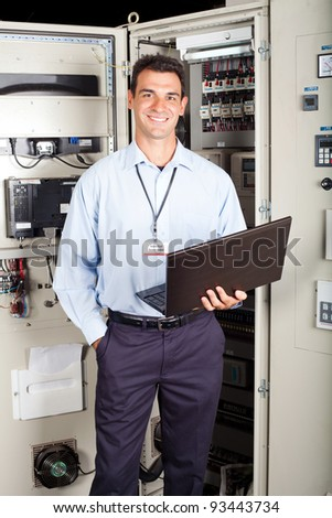 modern factory technician in front of industrial machine - stock photo