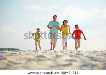 Modern family in casualwear running on sandy beach - stock photo