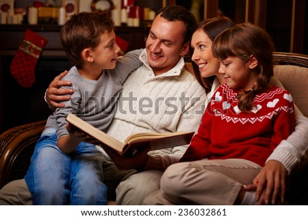 Modern family of father, mother, son and daughter reading together - stock photo
