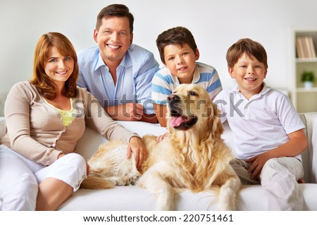 Modern family of four and their pet at home - stock photo