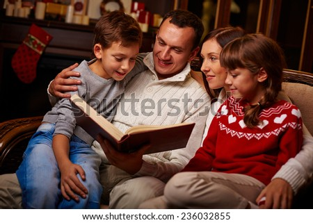 Modern family of four reading interesting tales at home - stock photo