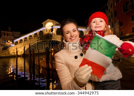 Modern family take the best of Christmas season by having a fascinating trip to Venice, Italy. Happy mother and daughter showing Italian flag in the front of Rialto Bridge