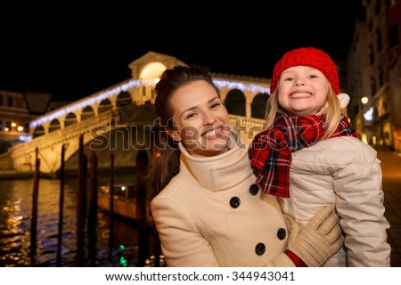 Modern family take the best of Christmas season by having a fascinating trip to Venice, Italy. Portrait of happy mother and daughter in the front of Rialto Bridge - stock photo