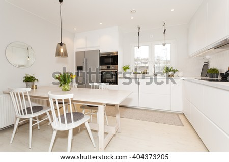 modern fancy kitchen with kitchen table and white cupboards - stock photo