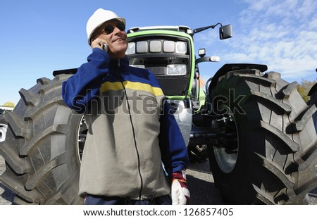 modern farmer in hardhat with large tractor - stock photo