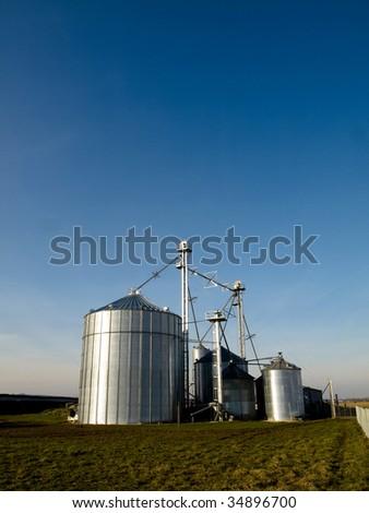Modern farmer silos factory in open fields - stock photo