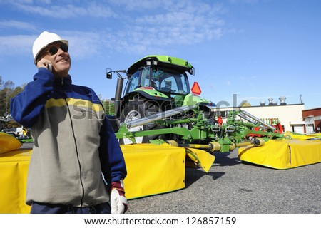 modern farmer with tractor and large mowers - stock photo