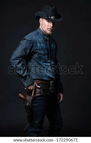 Modern fashion cowboy. Wearing black hat and blue jeans shirt. Pulling his gun. Blonde hair and beard. Studio shot against black.