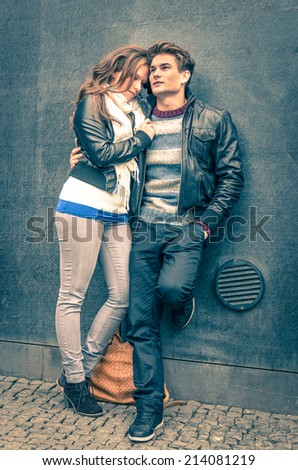 Modern fashion hipster couple of young lovers with autumn clothes ready for the upcoming winter - Deep moment of a love story with a cold vintage filtered look - stock photo