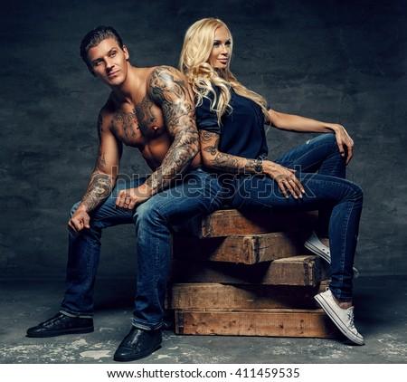 Modern fashionable couple. Shirtless tattoed man and sensual blond woman sitting on wooden blocks. - stock photo