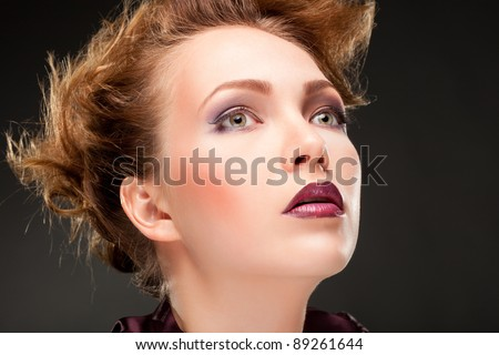Modern fashionable woman posing over gray background