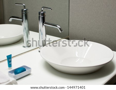 Modern faucet and sink in bathroom - stock photo