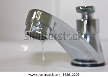 Modern faucet closeup with cute water drop - stock photo