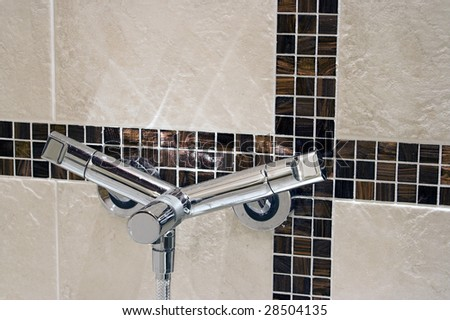 Modern faucet on a tiled wall - stock photo