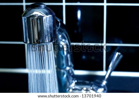 Modern Faucet with running water in blue - stock photo