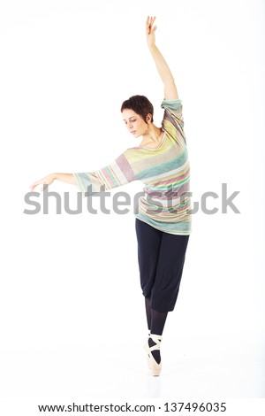 Modern female ballet dancer with black pants and a colorful striped jersey en pointe on a white background in various ballet positions.