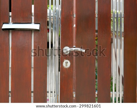 Modern fence door with handle and key lock - stock photo