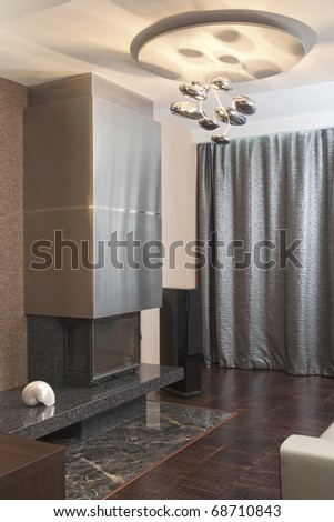 Modern fireplace in a room with a futuristic chandelier - stock photo