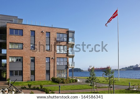 Modern Five Storey House On The Sea Shore With Norwegian Flag, Norway, Sunny