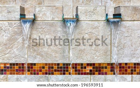Modern fountain detail. Waterfall drop design with decorative glass mosaic tile feature. - stock photo