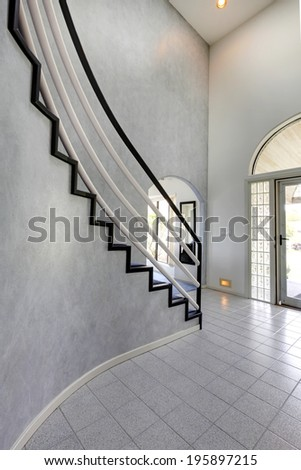 Modern foyer with high ceiling and tile floor. View of steep staircase with black and white railings - stock photo
