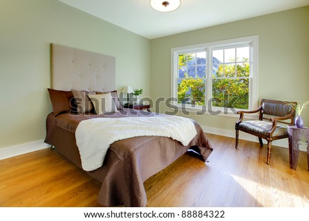 Modern fresh bedroom with oak floor and browns bedding - stock photo