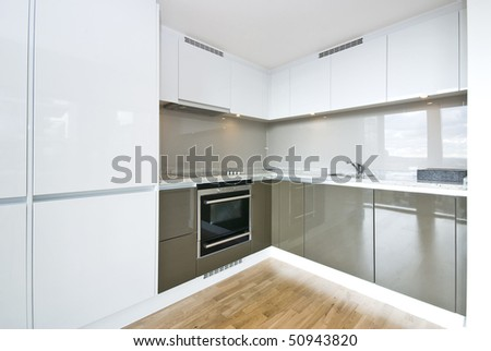 Modern fully fitted kitchen with kitchen appliances in army green and white - stock photo