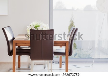 Modern furnished dining room with wooden table and leather chairs - stock photo
