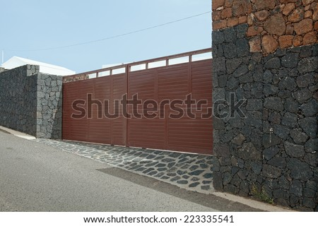 Modern garage door. Large automatic sliding garage door. Walls made of volcanic rock. Entrance to wealthy residence on island Lanzarote. - stock photo