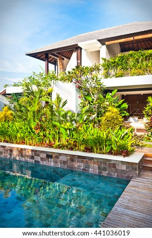 Modern garden and a swimming pool in a luxury house with blue sky background - stock photo