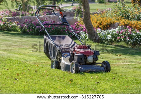 Modern gasoline lawn mower on a green meadow. Gardening equipment - stock photo