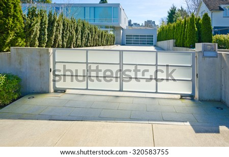 Modern gates with driveway to the luxury house with double doors garage. North America. - stock photo