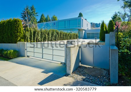 Modern gates with driveway to the luxury house with double doors garage. North America.