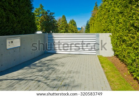 Modern gates with nicely paved driveway. driveway. North America. - stock photo