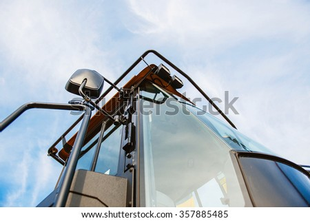 Modern generic tractor cabine against blue clear sky - stock photo